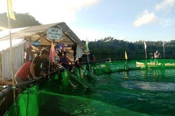 Männer stehen um einen der schwimmenden Käfige herum