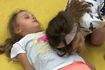 Ein Mädchen hört mit dem Ohr den Herzschlag eines anderen Mädchens ab.