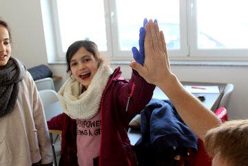 Ein Mädchen, das einen Einmal-Handschuh trägt, gibt ein High-Five
