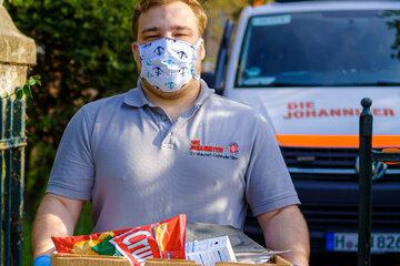 Johanniter-Helfer mit Einkäufen während der Corona-Pandemie.