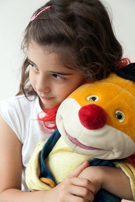 Ein Mädchen mit Kuscheltier im Arm.