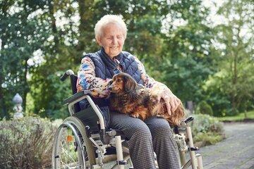Eine Bewohnerin kuschelt mit einem Hund