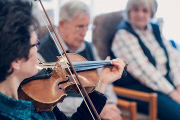 Zwei Bewohnende lauschen einer Violinistin beim Konzert