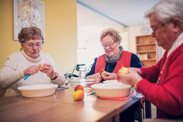 Drei Seniorinnen beschäftigen sich mit dem Schälen von Äpfeln im Johanniter-Stift Gronau