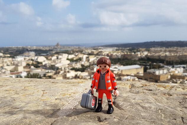 Playmobil-Figur der Johanniter steht in Malta. Im Hintergrund sind das Meer und die tollen Wohnhäuser der Inselbewohner zu sehen.
