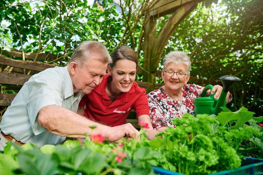 Eine Pflegerin der Johanniter ist mit zwei älteren Pflegepersonen im Garten.