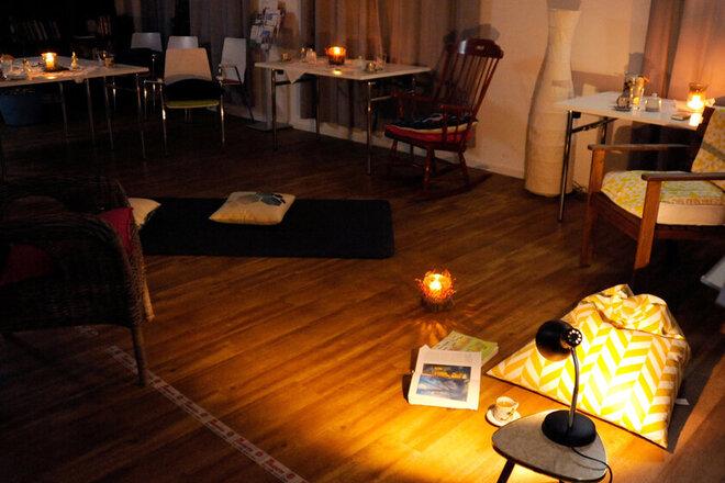 Gemütlicher Raum mit vielen kleine Lampen, Kerzen und weitauseinander gestellten Tischen. In der Mitte des Raumes liegt ein Buch, aus dem gerade vorgelesen wurde.