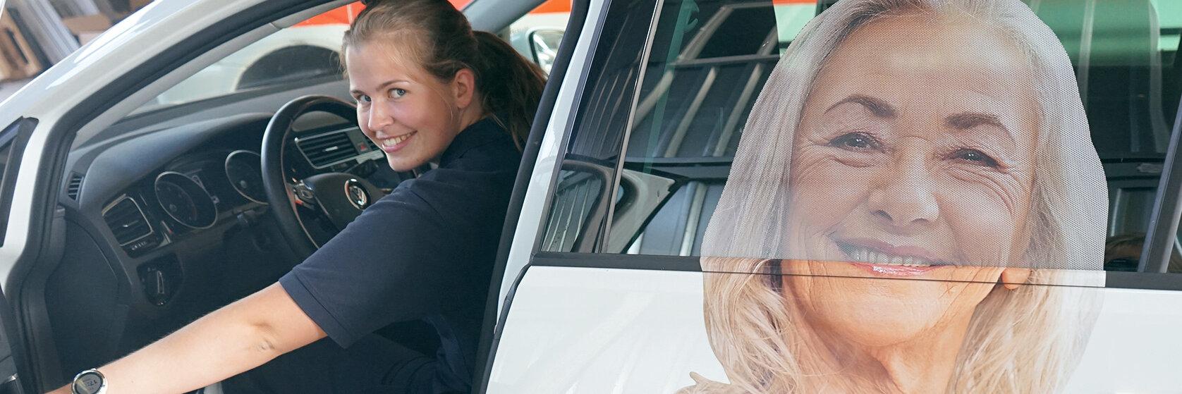 Johanniterin in dunkelblauer Dienstkleidung am Steuer eines Wagens mit Hausnotruf-Werbung