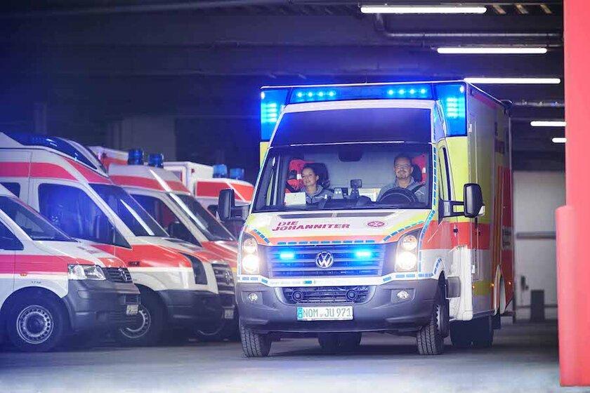 Rettungswagen fährt mit Blaulicht aus der Halle