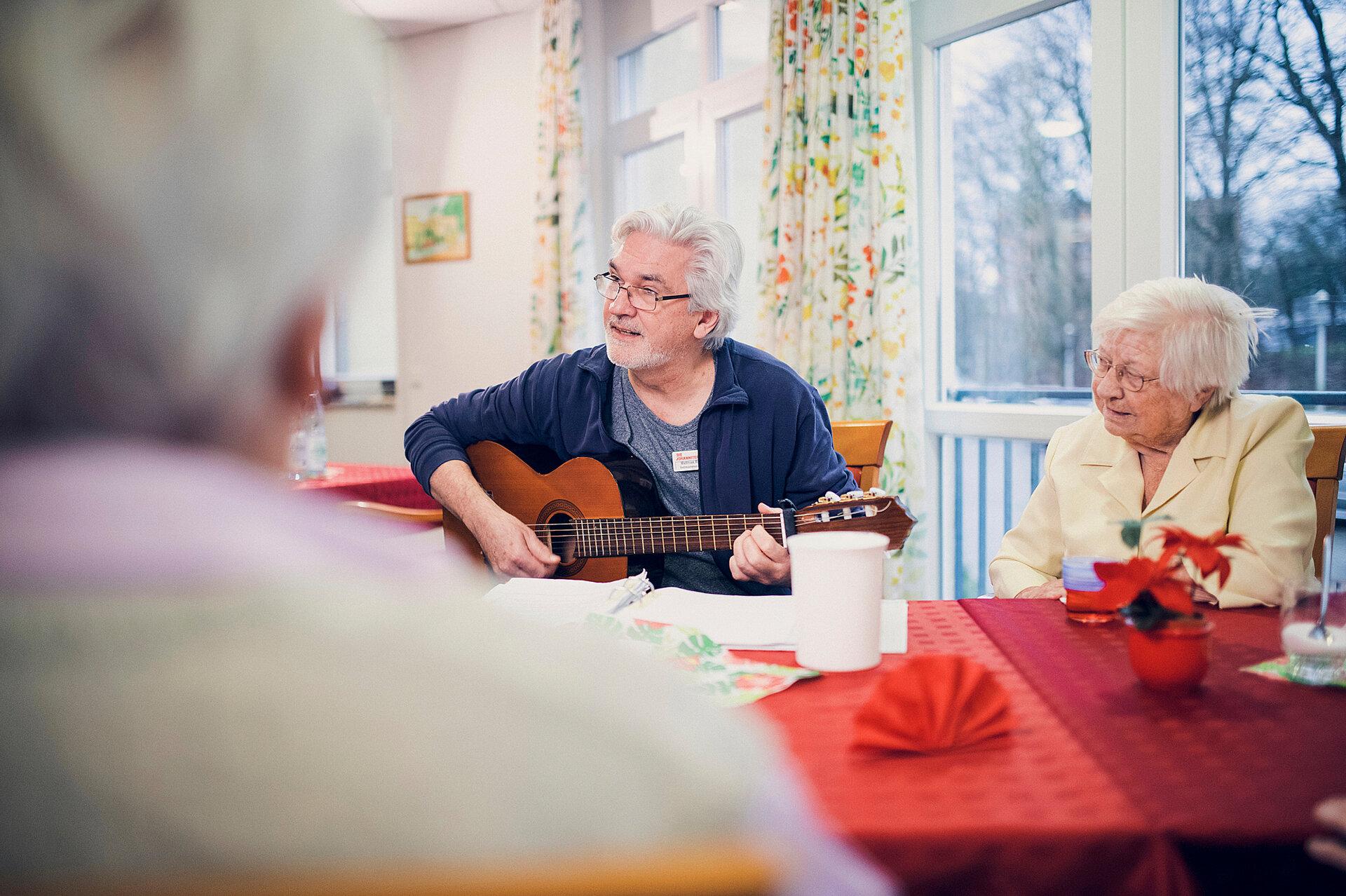 Ein Mitarbeiter spielt Gitarre und eine Gruppe von Bewohnenden hört zu