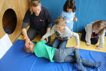 Eine Erzieherin zeigt drei Kindern die stabile Seitenlage.