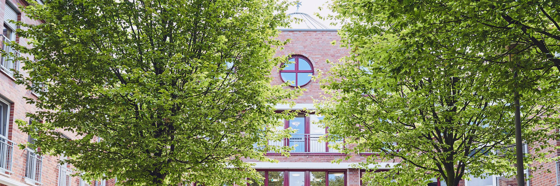 Schön gestalteter Vorplatz mit zwei Bäumen und gegenüberstehenden Bänken zum Johanniter-Stift Wuppertal