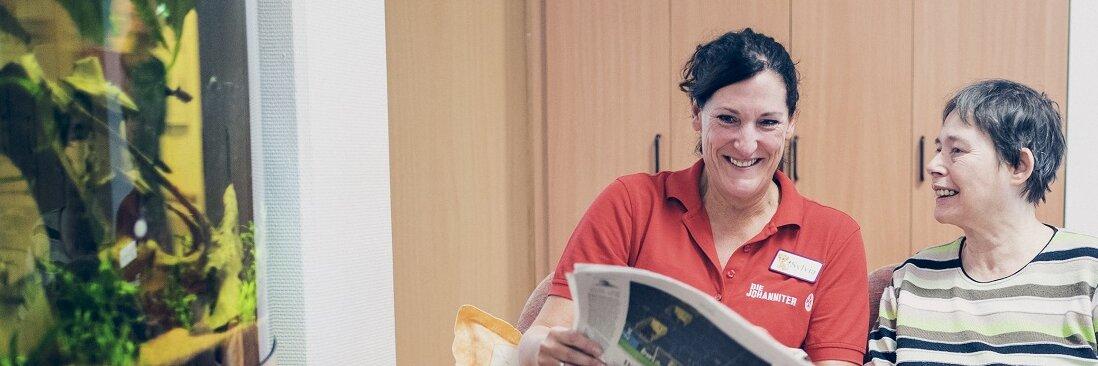 Eine Mitarbeiterin liest mit einer Bewohnerin eine Zeitung