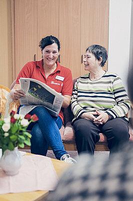 Eine Dame liest einer Seniorin vor