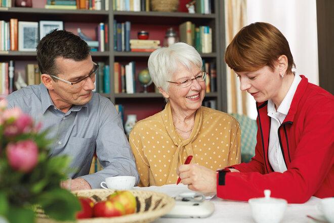 Eine Frau berät einen Mann und eine ältere Dame