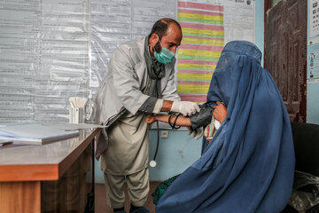 A man measures the blood pressure of a woman, both wear a mouth-nose covering mask.