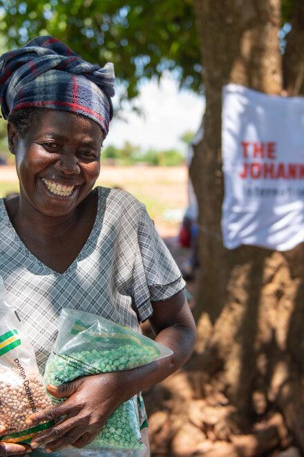 Eine Frau mit großem Lächeln und Saatgut in den Händen