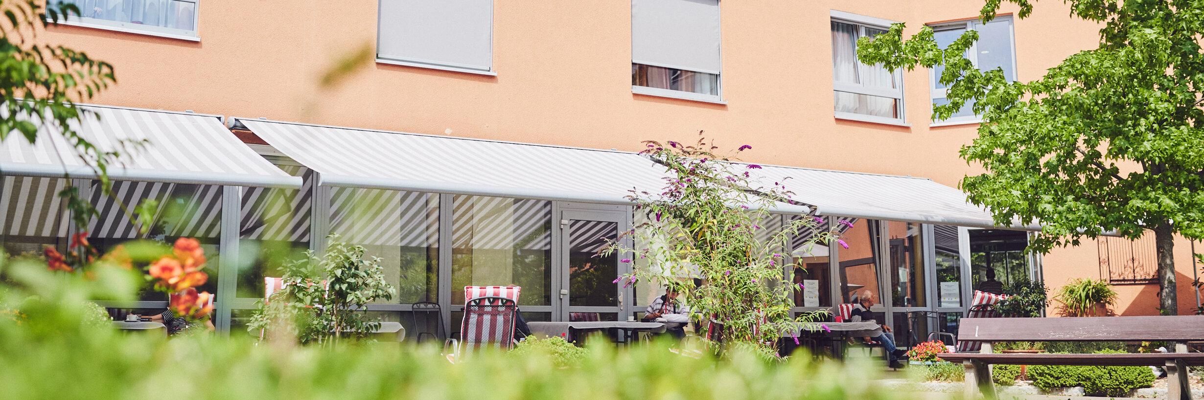 Sicht zur gemütlichen Innenhofseite und den überdachten Sitzbereichen des Johanniter-Hauses Köln Zollstock.