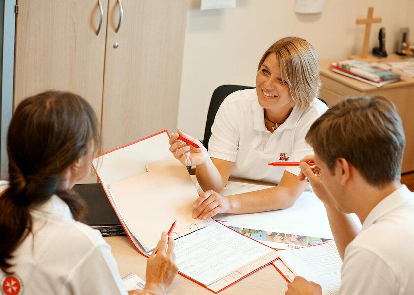 Drei Pflegekräfte schauen gemeinsam Unterlagen durch
