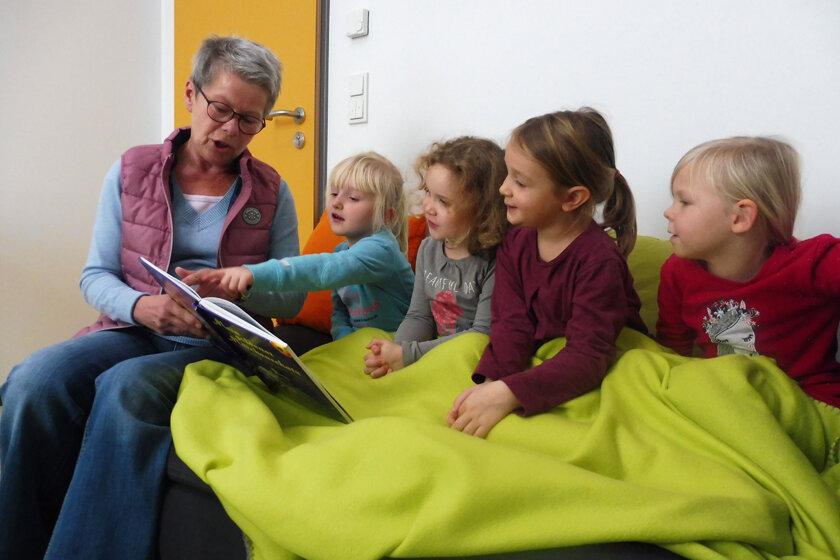 Eine Lesepatin sitzt mit den Kindern auf dem Sofa und liest ihnen vor. Alle Kinder sind unter eine hellgrüne Wolldecke gekuschelt und schauen mit ins das Buch hinein.