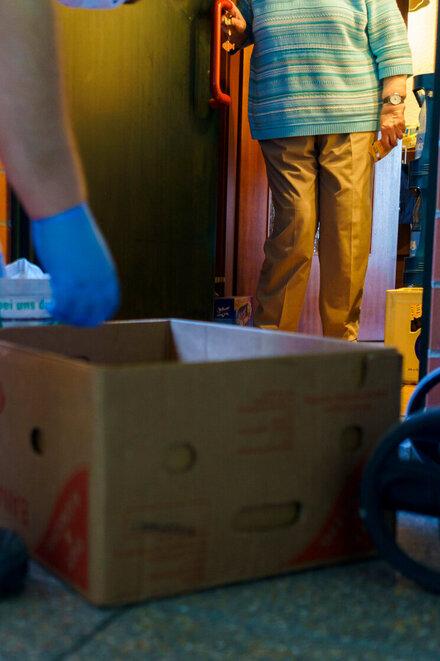 Ein Helfer der Johanniter-Unfall-Hilfe liefert Einkäufe an eine ältere Frau.
