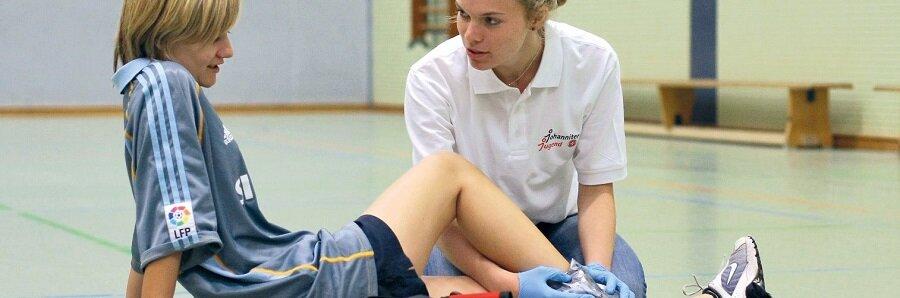 Schulsanitäterin kümmert sich um eine Schülerin nach einem Sportunfall.