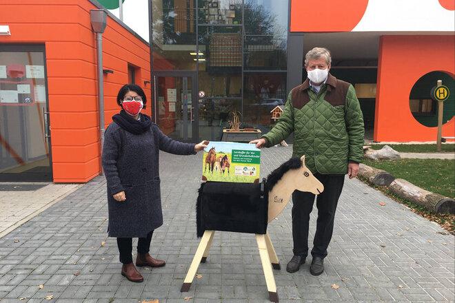 Kitaleiterin und Carl Garf von Hardenberg stehen vor der Kita Elementum und zeigen das Holzpferd inklusive Lernkoffer.