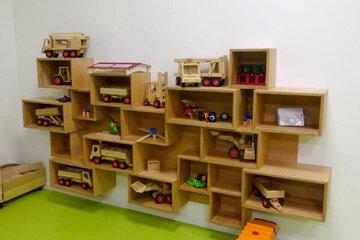 Wandregal mit zahlreichen Spielsachen wie beispielsweise kleine Eisenbahnen, Traktoren und Co.
