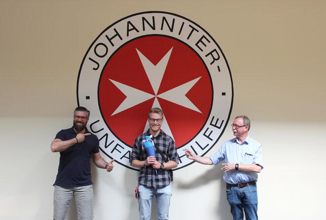 Dennis Schütte, Jan Gress und Arnold-Friedrich von Zepelin stehen von dem Johanniter-Logo, welches Jan vor vielen Jahren an die Wand des Hildesheimer Konferenzsaals gemalt hat.