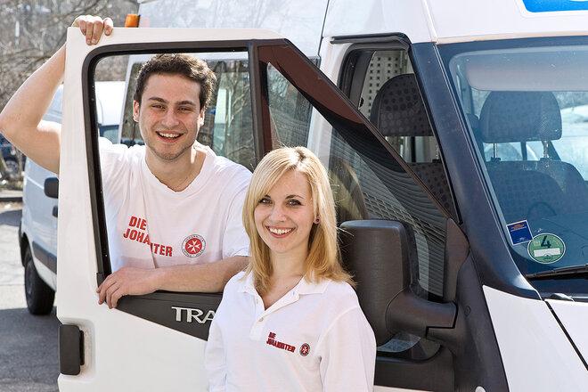 Ein junger Mann und eine junge Frau, die ein Freiwilliges Soziales Jahr bei den Johannitern, machen neben einem Dienstauto der Johanniter.