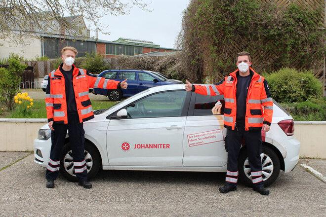 Zwei Bundesfreiwilligendienstler stehen vor den Hausnotruf-Einsatz-Wagen.