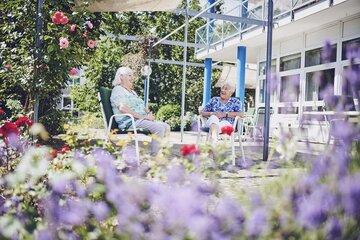 Zwei Bewohnerinnen sitzen im Garten des Johanniter-Pflegewohnhaus Haus Kielwein