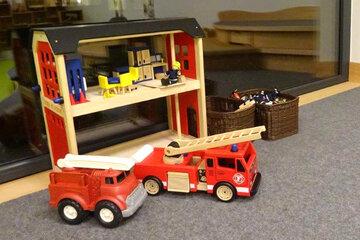 Kleine Feuerwehrautos und Feuerwache aus Holz zum Spielen und Entdecken.