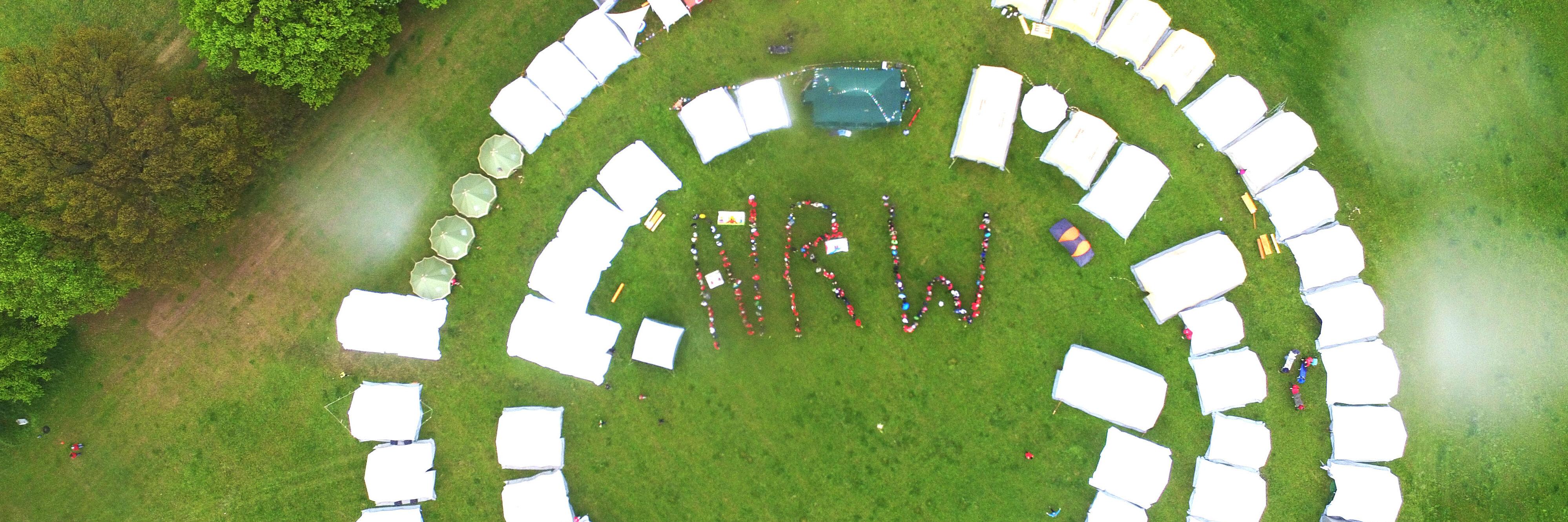 Eine Luftaufnahme von Zelten, die im Kreis angeordnet sind. In der Mitte bilden Menschen die Buchstaben N R W.