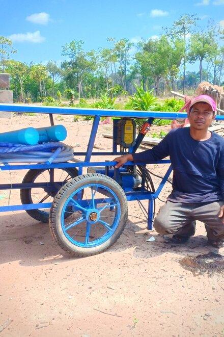 Ein Mann mit einer großen Solarzelle neben sich. Diese betreibt eine Wasserpumpe.