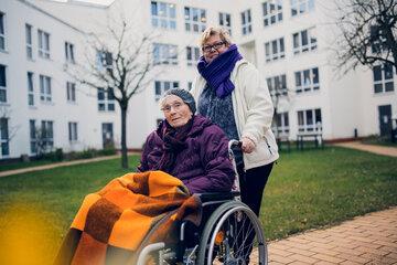 Bewohnerin im Rollstuhl wird von der Betreuerin im Garten der Einrichtung Haus Lübeck spazieren gefahren