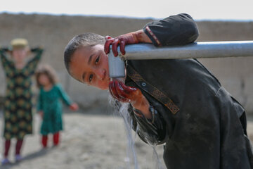 A little boy drinks from a drinking fountain
