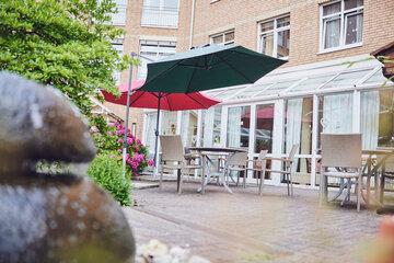 Tisch, Gartenstühle und Sonnenschirm vor dem Johanniter-Stift Erkelenz