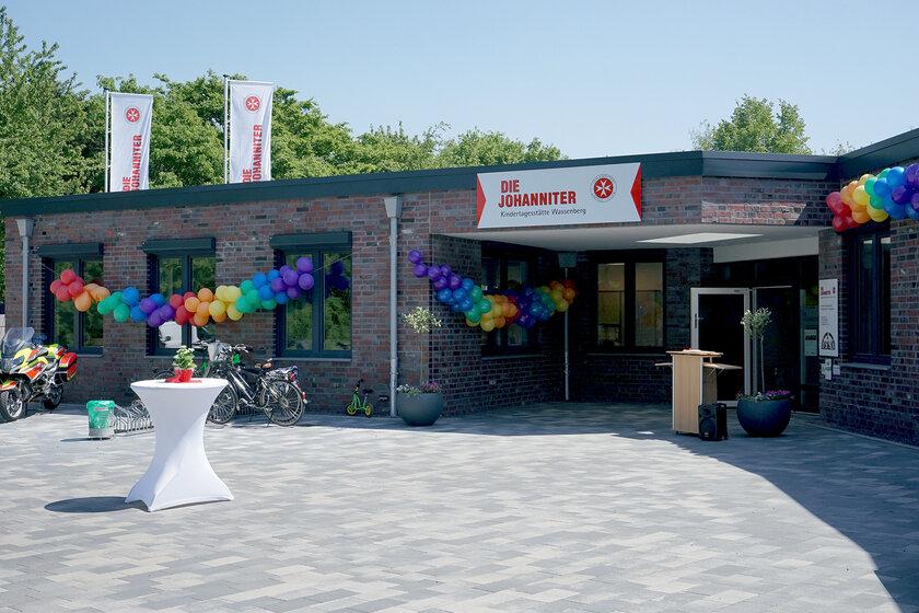 Vorplatz und Eingangsbereichs eines einstöckigen Gebäudes mit dunklen Klinkern und dunkelgrauen Fensterrahmen geschmückt mit Johanniter-Fahnen und Luftballons