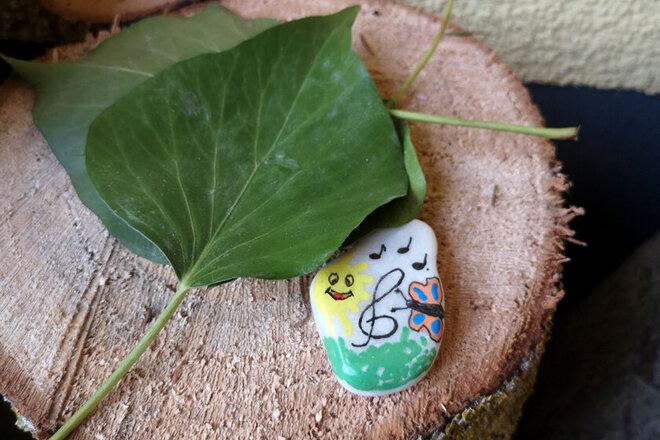 Kleiner Stein bemalt mit einer Sonne, Wiese und einem bunten Schmetterling.