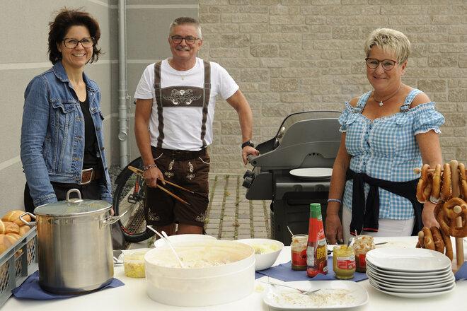 Ein Mann und eine Frau in bayrischer Tracht mit einer anderen Frau am Buffet