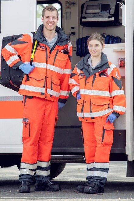 Mitarbeitende aus dem Rettungsdienst vor Rettungswagen