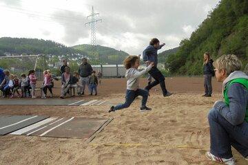 Ein Vater und sein Sohn machen Weitsprung in den Sand auf einem Sportplatz.