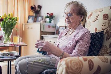 Eine Bewohnerin strickt mit vier Nadeln Socken