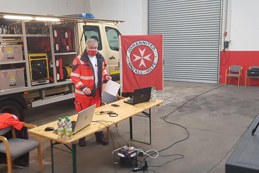 Vor einem Katastrophenschutz-Fahrzeug steht ein Mann in Johanniter-Kleidung, der von einer Kamera gefilmt wird.