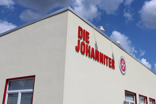 Ein gebes Flachdachgbäude mit Johanniter-Logo