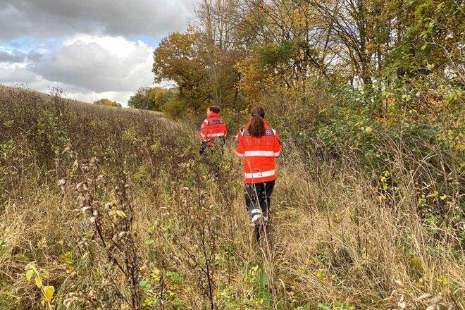 Mitgliederinnen der Rettungshundestaffel Südniedersachsen suchen in einem Feld am Waldrand nach der Vermissten.