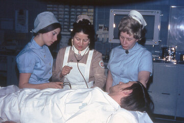 Drei Johanniter-Schwesternhelferinnen stehen am Krankenbett und versorgen den Patienten.