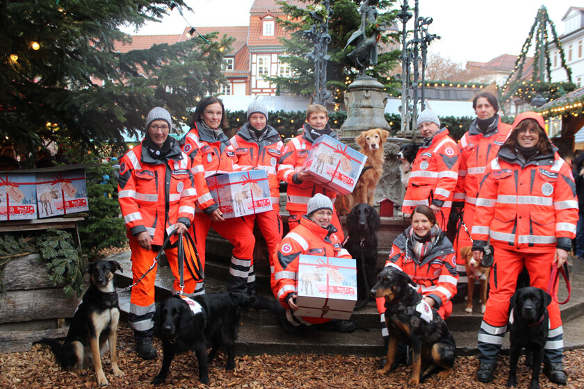 Mitglieder und Hunde der Rettungshundestaffel Südniedersachsen zeigen ihre gepackten Pakete. Im Hintergrund sind die Tannen und Lichterketten des Weihnachrtsmarktes zu sehen.