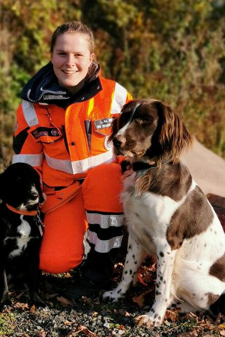 Lena Marie Berlitz sitzt mit ihren beiden Hunden an einem Feldweg.